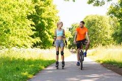 Coppie felici con i rollerblades e la guida della bicicletta fotografie stock