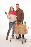 Coppie felici con i sacchetti della spesa della drogheria in carrello fotografia stock libera da diritti