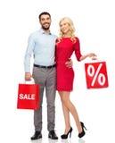 Coppie felici con i sacchetti della spesa rossi Immagine Stock Libera da Diritti