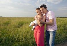 Coppie felici con il bambino in prato Immagine Stock