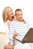 Coppie felici con il computer portatile fotografia stock