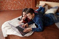 Coppie felici con il computer portatile che comperano online a casa, Internet di lettura rapida a letto, sorridere e divertiresi Fotografia Stock Libera da Diritti