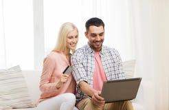 Coppie felici con il computer portatile e la carta di credito a casa Immagini Stock Libere da Diritti