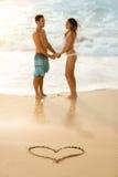 Coppie felici con il cuore di tiraggio sulla spiaggia sabbiosa fotografia stock