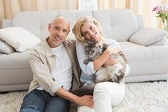 Coppie felici con il gatto dell'animale domestico sul pavimento fotografia stock
