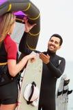 Coppie felici con il kiteboard sopra il giorno di estate Immagine Stock