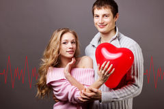 Coppie felici con il pallone rosso. Giorno di biglietti di S. Valentino Immagini Stock Libere da Diritti