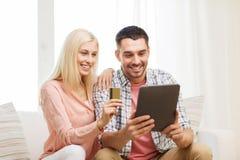Coppie felici con il pc della compressa e la carta di credito Immagini Stock