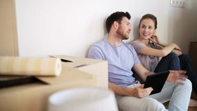 Coppie felici con il pc della compressa a nuova casa stock footage