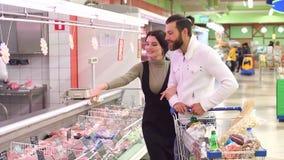 Coppie felici con la carne d'acquisto del carrello alla drogheria o al supermercato video d archivio