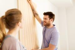 Coppie felici con la carta da parati che ripara nuova casa Immagine Stock