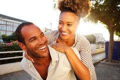 Coppie felici con la donna di trasporto dell'uomo in città fotografie stock libere da diritti