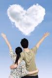 Coppie felici con la nuvola di forma del cuore immagine stock