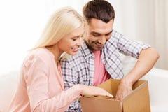 Coppie felici con la scatola del pacchetto a casa Immagini Stock Libere da Diritti