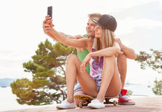 Coppie felici con la seduta sul pattino e la presa del selfie Immagini Stock Libere da Diritti