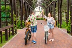 Coppie felici con le bici che danno gli alti cinque in arco Fotografia Stock Libera da Diritti