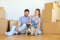 Coppie felici con le scatole ed il cane che si muovono verso la nuova casa immagini stock libere da diritti