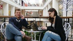 Coppie felici con lo smartphone ed il computer portatile in caffè Equipaggi la conversazione sul telefono, donna che lavora al ta fotografie stock libere da diritti