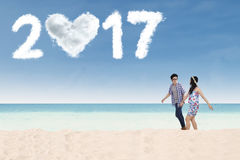 Coppie felici con 2017 sulla spiaggia Immagine Stock