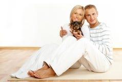 Coppie felici con un cucciolo Fotografia Stock