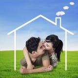 Coppie felici con una casa di sogno Fotografia Stock Libera da Diritti