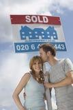 Coppie felici dal segno venduto contro il cielo immagine stock libera da diritti