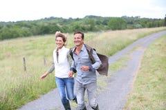 Coppie felici degli agricoltori che corrono nella campagna Fotografia Stock