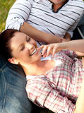 Coppie felici degli allievi che si siedono sull'erba Fotografia Stock Libera da Diritti