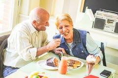 Coppie felici degli anziani che mangiano i pancake in un ristorante della barra - pensionati divertendosi godendo del pranzo insi fotografia stock