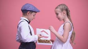 Coppie felici dei bambini che mangiano insieme le caramelle di cioccolato, data romantica, amore stock footage