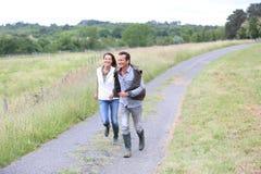 Coppie felici dei selezionatori che camminano nella campagna Immagini Stock