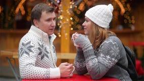 Coppie felici dei turisti in vestiti caldi che bevono caffè dalle tazze in Città Vecchia, giovane famiglia sul Natale giusto stock footage
