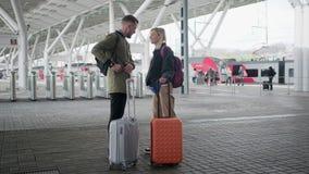 Coppie felici dei viaggiatori che stanno sulla piattaforma con le valigie prima della partenza stock footage