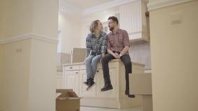 Coppie felici del ritratto giovani che si siedono sul tavolo da cucina in un nuovo appartamento che discute la disposizione della video d archivio
