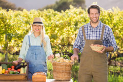 Coppie felici dell'agricoltore che presentano il loro alimento locale Fotografie Stock