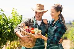 Coppie felici dell'agricoltore che tengono un canestro delle verdure Fotografie Stock