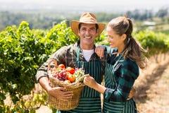 Coppie felici dell'agricoltore che tengono un canestro delle verdure Fotografie Stock Libere da Diritti