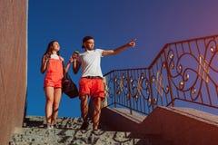 Coppie felici dell'istituto universitario nell'amore che mangia caffè e che cammina nella città Tipi che camminano giù le scale Fotografia Stock Libera da Diritti