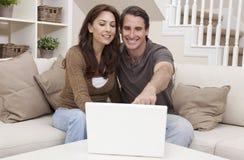 Coppie felici della donna & dell'uomo per mezzo del computer portatile Immagini Stock Libere da Diritti