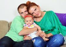 Coppie felici della famiglia con la neonata fotografia stock