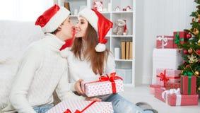 Coppie felici della famiglia con un regalo sul Natale a casa Fotografia Stock Libera da Diritti