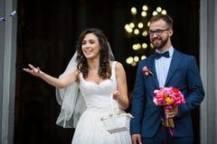 Coppie felici della persona appena sposata che escono da chiesa, tenente mazzo e fotografia stock