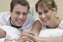 Coppie felici della persona appena sposata a letto fotografia stock