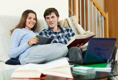 Coppie felici dello studente che si siedono sullo strato Fotografia Stock