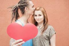 Coppie felici di giorno di biglietti di S. Valentino che tengono simbolo rosso del cuore Immagine Stock Libera da Diritti