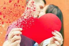 Coppie felici di giorno di biglietti di S. Valentino che tengono simbolo rosso del cuore Immagine Stock