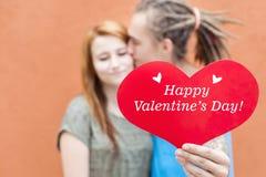 Coppie felici di giorno di biglietti di S. Valentino che tengono simbolo rosso del cuore Fotografia Stock