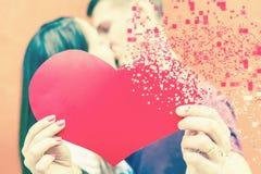 Coppie felici di giorno di biglietti di S. Valentino che tengono simbolo rosso del cuore Immagini Stock Libere da Diritti