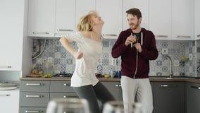 Coppie felici di mattina a casa le giovani recentemente wed il dancing che ascolta la musica in cucina video d archivio