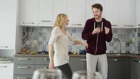 Coppie felici di mattina a casa le giovani recentemente wed il dancing che ascolta la musica in cucina archivi video